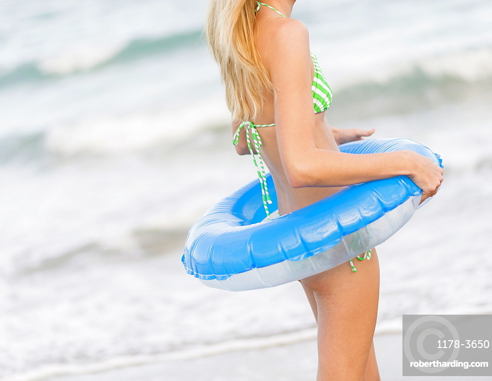 Young woman with inner tube, Jupiter, Florida, USA