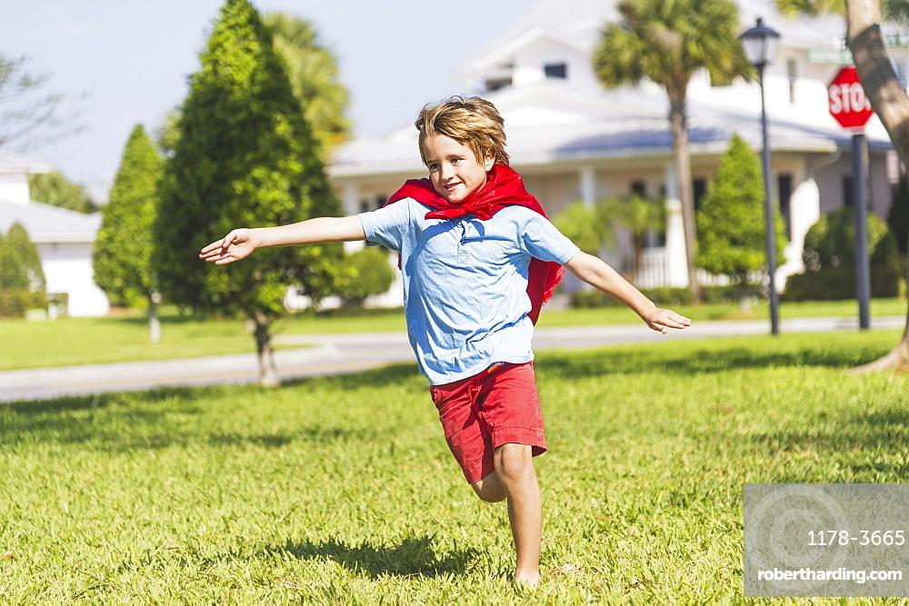 Boy (8-9) running with cape, Jupiter, Florida, USA