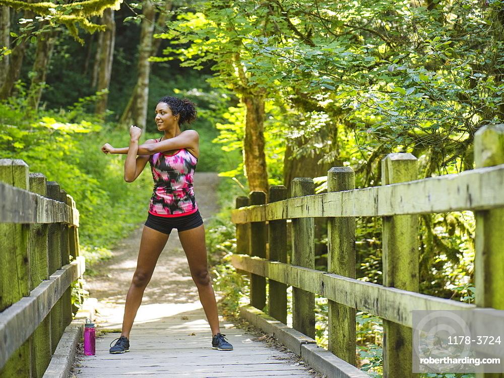 Young women stretching on footbridge, USA, Oregon, Portland
