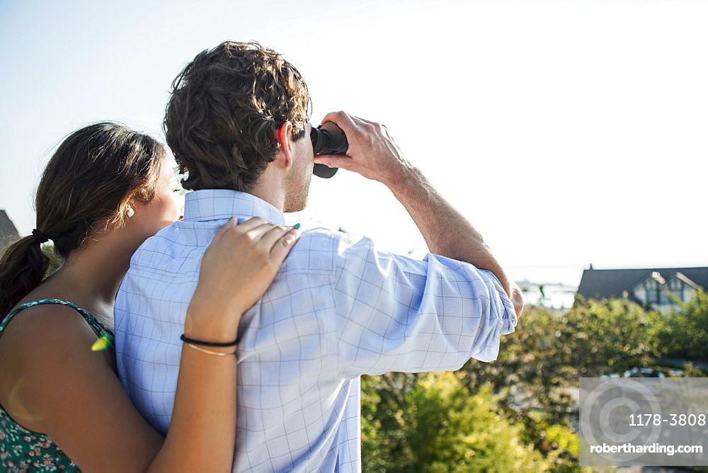 Rear view of couple, man looking through binoculars, USA, Washington, Everett