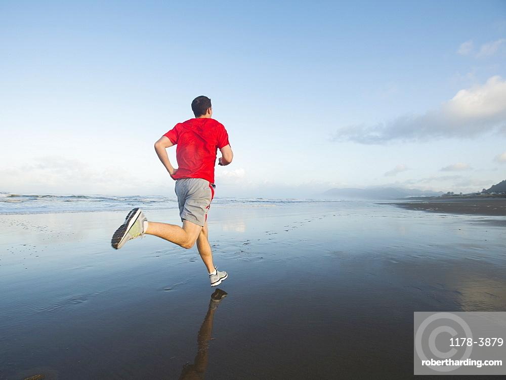 Young adult man running on beach, Rockaway Beach, Oregon