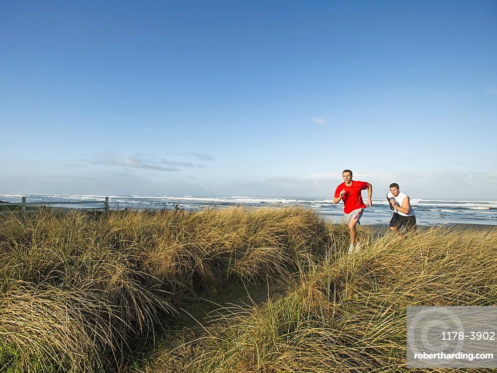 Young adult men running on dune, Rockaway Beach, Oregon