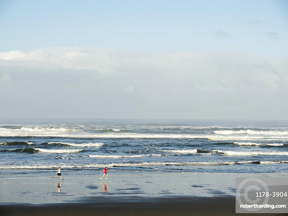 Young adult men running on beach, Rockaway Beach, Oregon