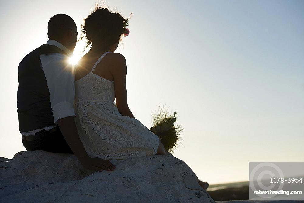 Newlywed couple looking at setting sun