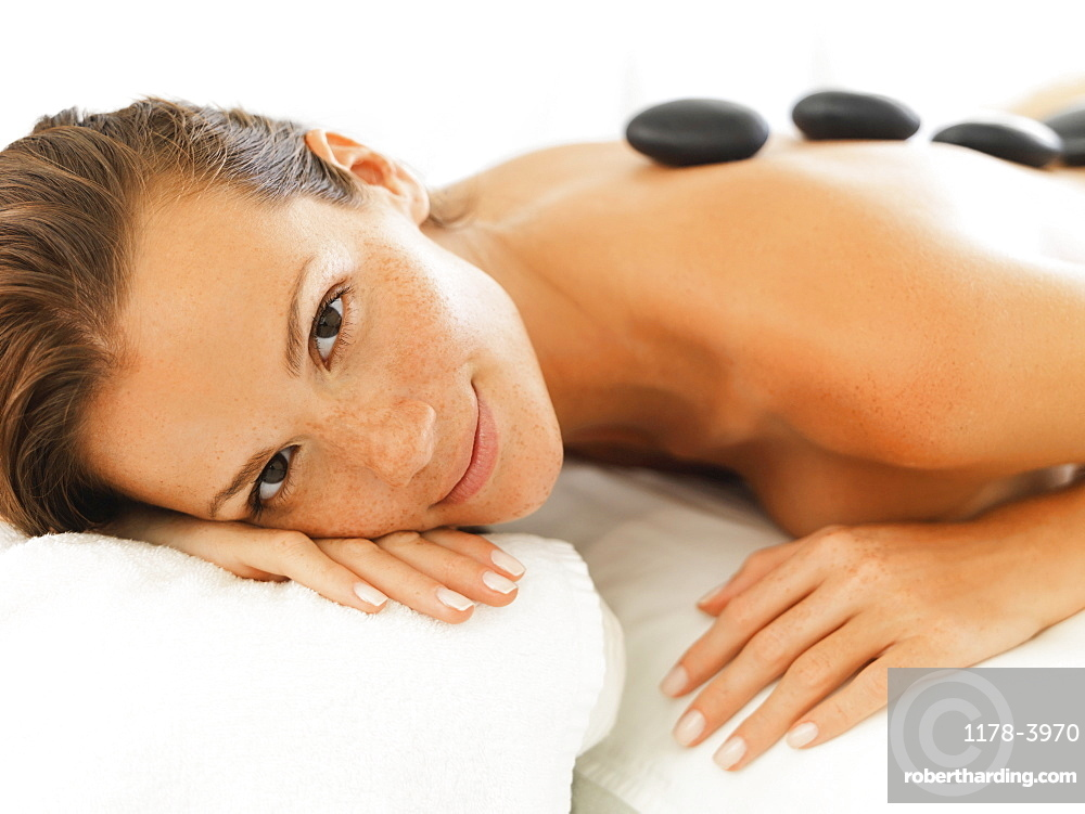 Woman relaxing while getting stone massage