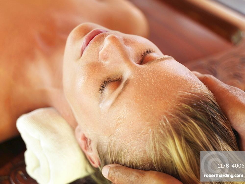 Mid adult woman receiving head massage