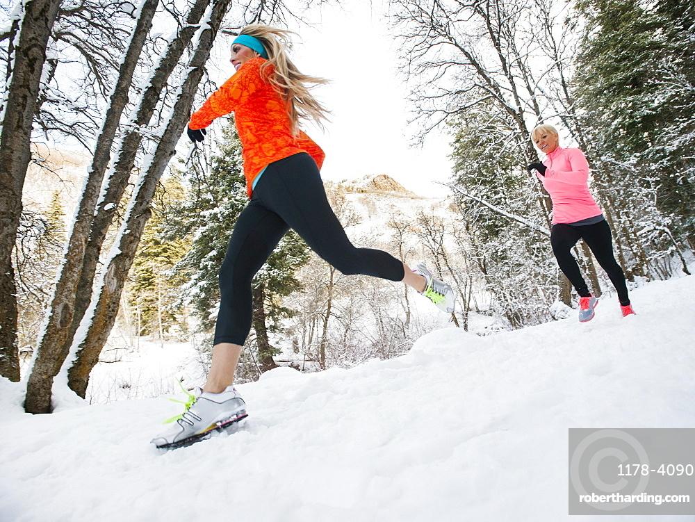 Two women jogging in winter forest, Salt Lake City, Utah USA