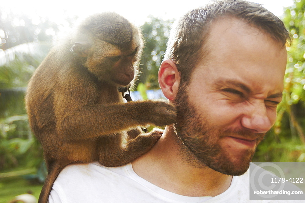 Portrait of adult man with macaque monkey sitting on his shoulder, Thailand