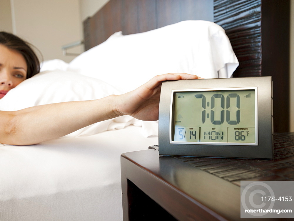 Young attractive woman turning off alarm clock