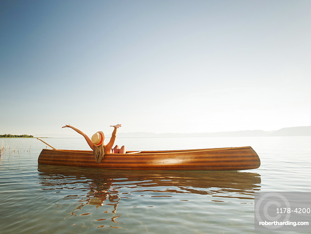 Young woman relaxing in canoe with arms raised