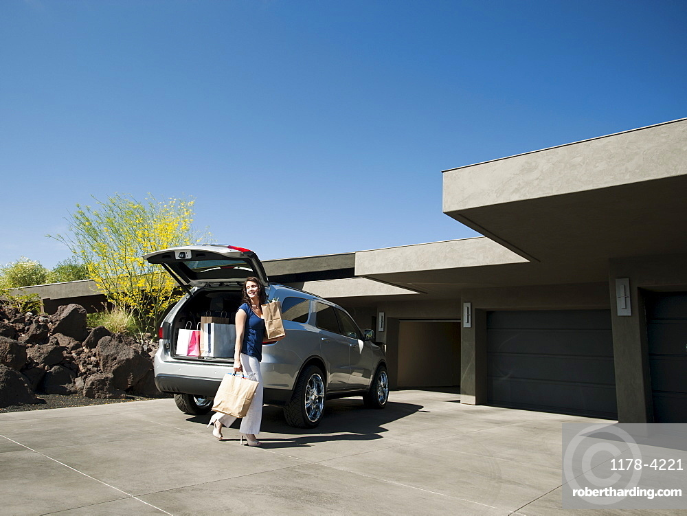 Woman with groceries leaving car, USA, Utah, St George
