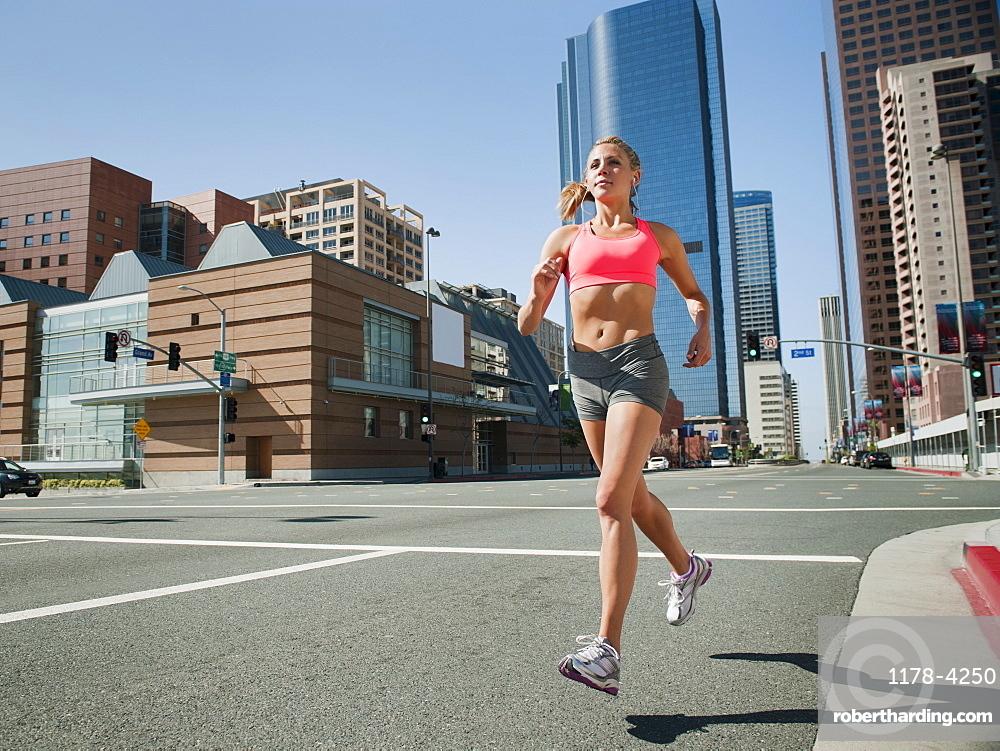 USA, California, Los Angeles, Young woman running on city street, USA, California, Los Angeles