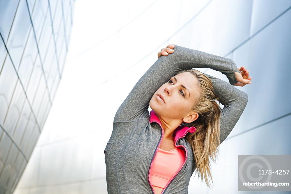 USA, California, Los Angeles, Young woman stretching near modern building, USA, California, Los Angeles