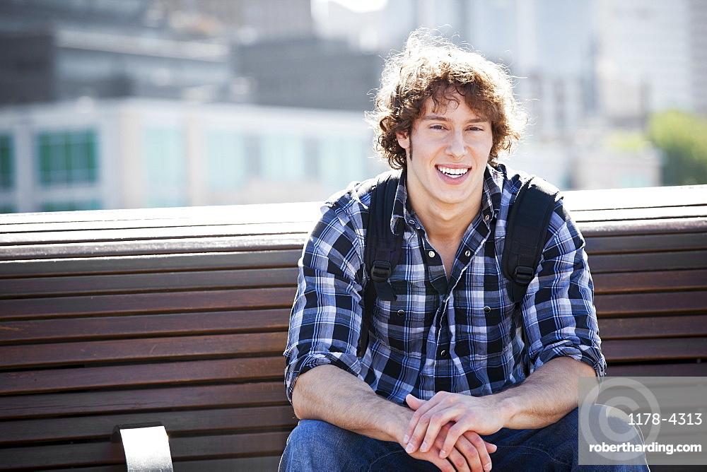 USA, Washington, Seattle, Young man sitting on bench