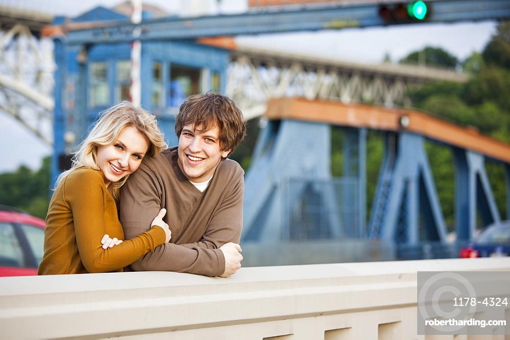 Portrait of young couple on bridge