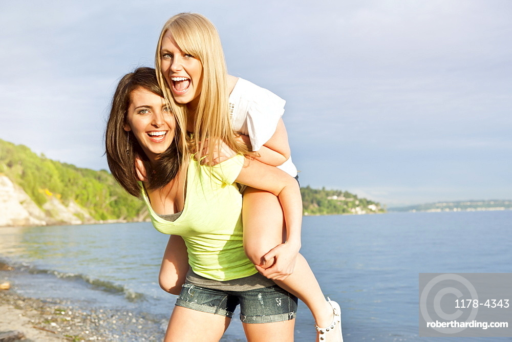 Portrait of two young women piggy-backing on beach