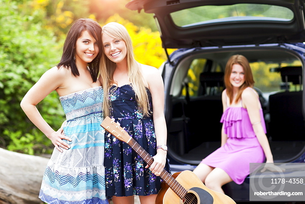 Portrait of young women with guitar by car