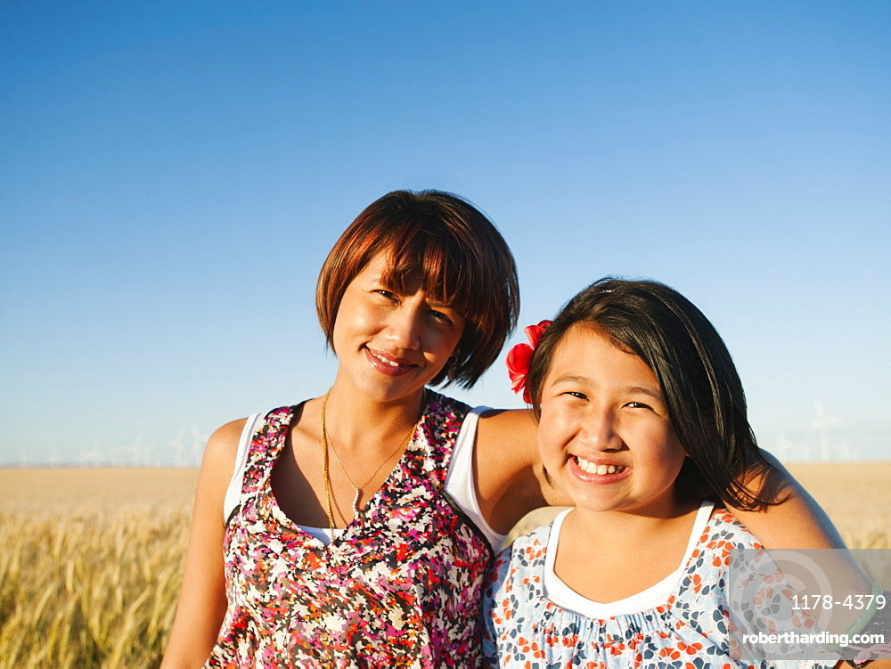 Mother and daughter (10-11) standing in wheat field