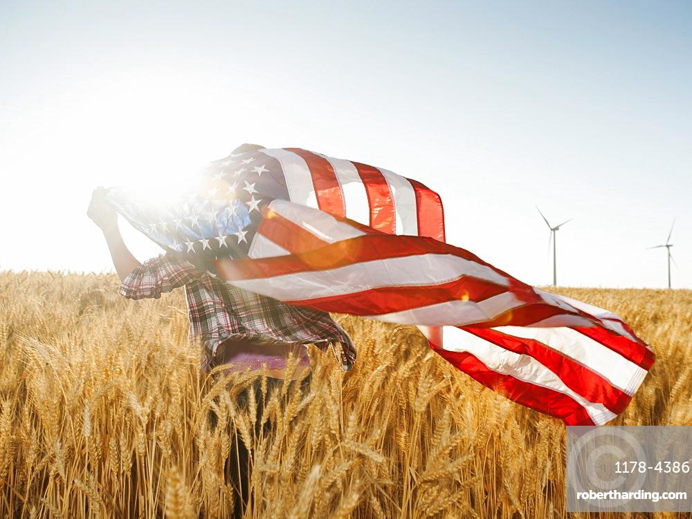 Girl (12-13) flying american flag in wheat field