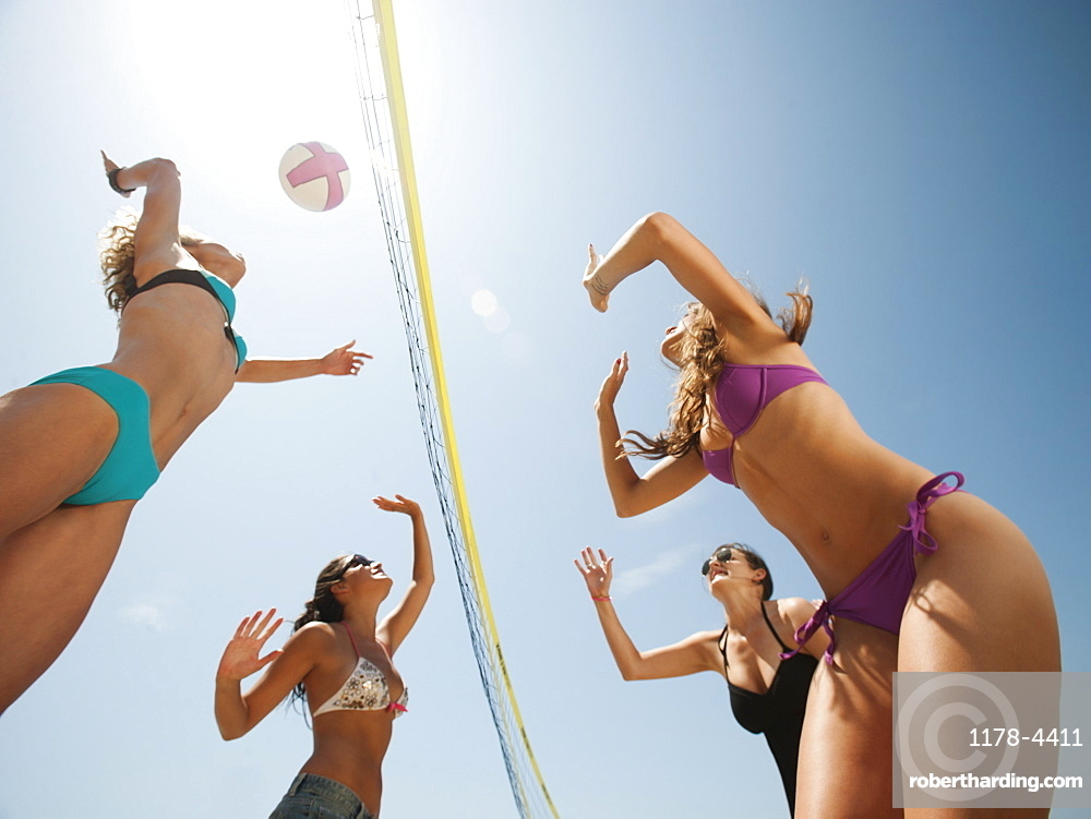 Group of young women playing beach volleyball