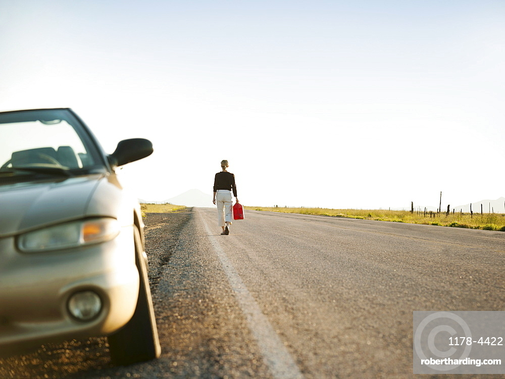 Woman carrying canister walking along empty road, her car parked on roadside
