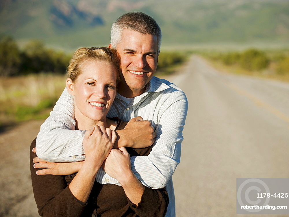 Mid adult couple embracing on empty road