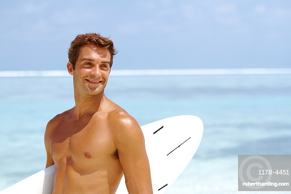 Shirtless young man holding surfboard