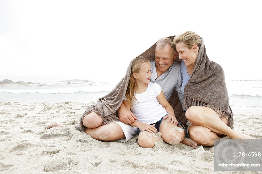Smiling parents with daughter (10-11) on coastline covered by blanket