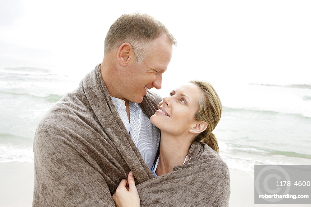 Embraced couple covered by blanket looking each other