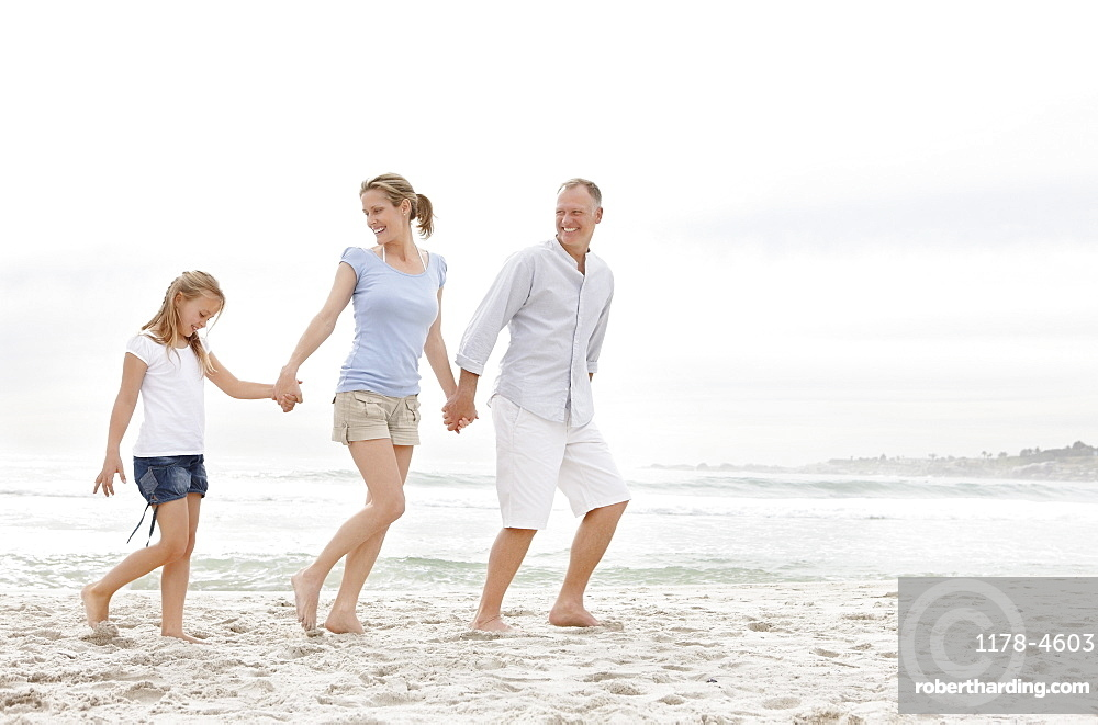 Parents with daughter (10-11) walking on beach