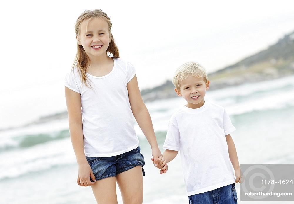 Girl (10-11) and boy (4-5) on beach