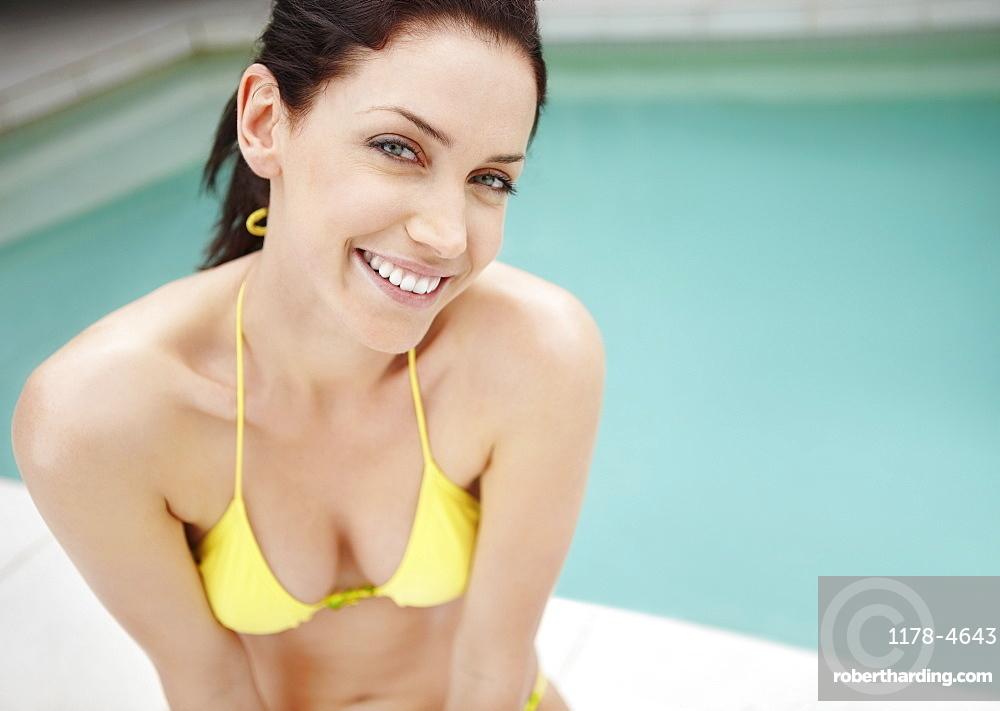 Woman wearing bikini sitting beside pool