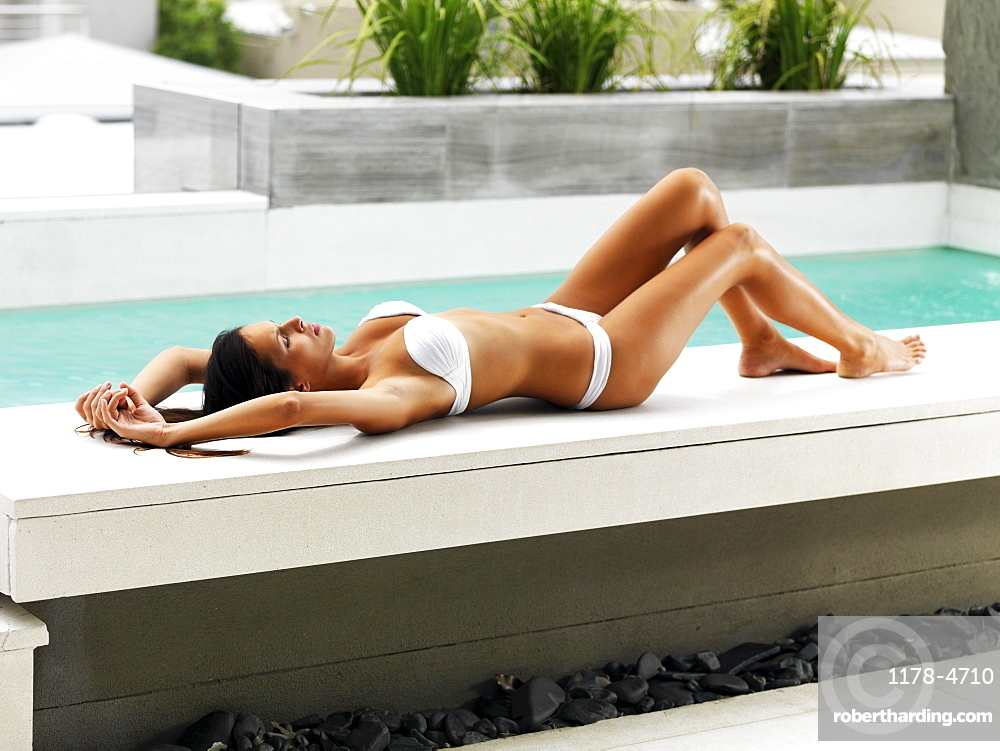 Woman sunbathing beside pool