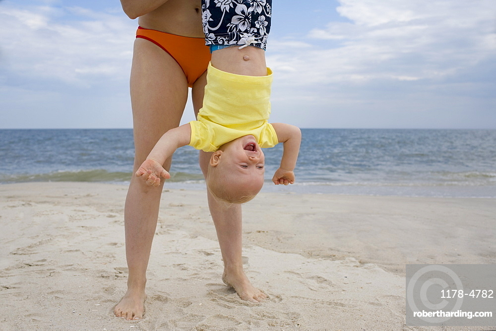 Mother holding baby boy upside-down on beach