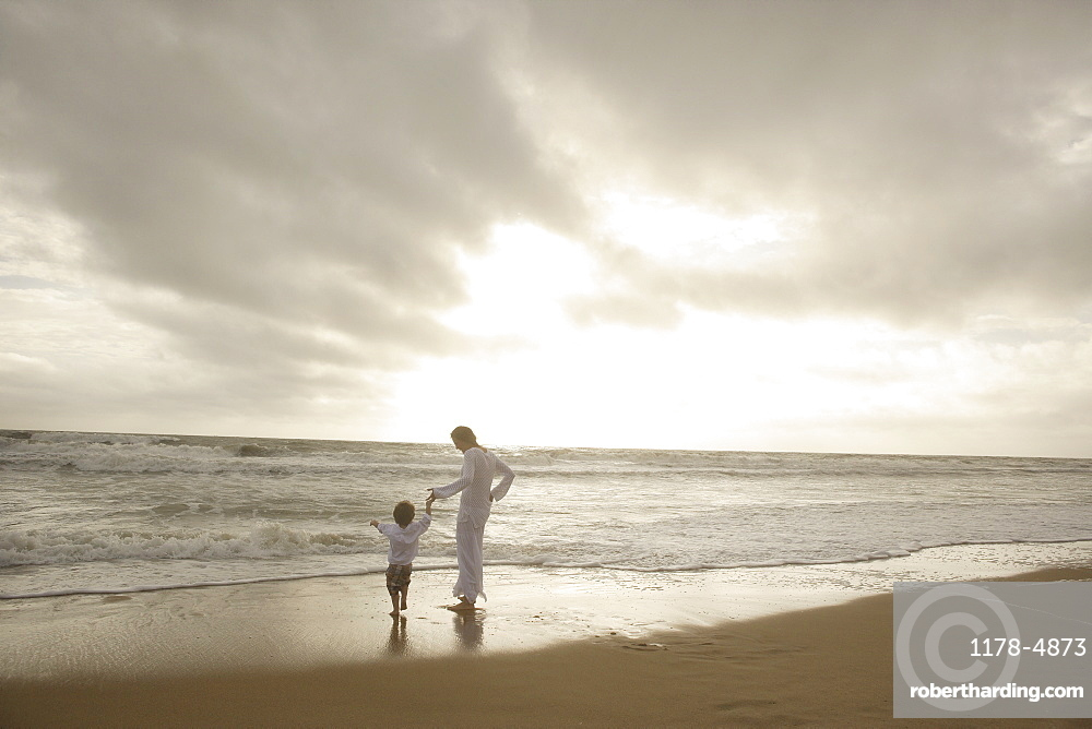 Mother and child holding hands at beach