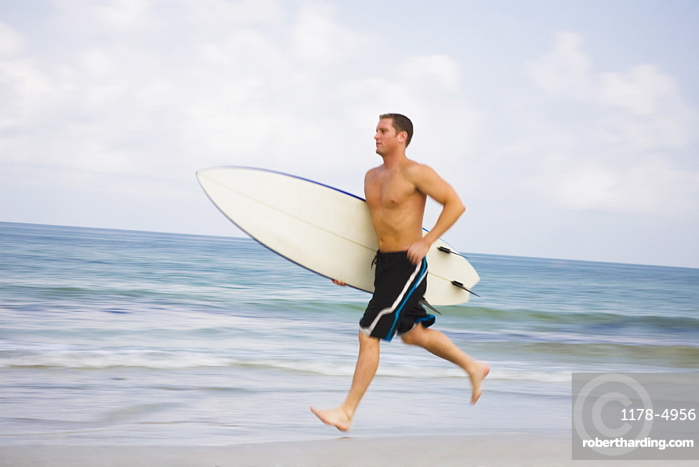 Bare-chested man running with surfboard
