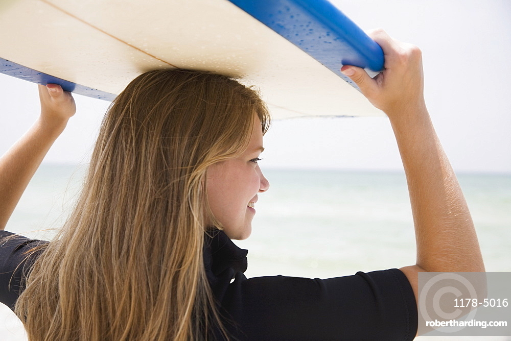 Girl holding surfboard on head, Florida, United States