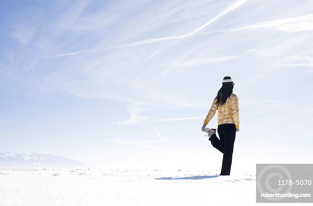 Woman stretching on snow, Colorado, USA