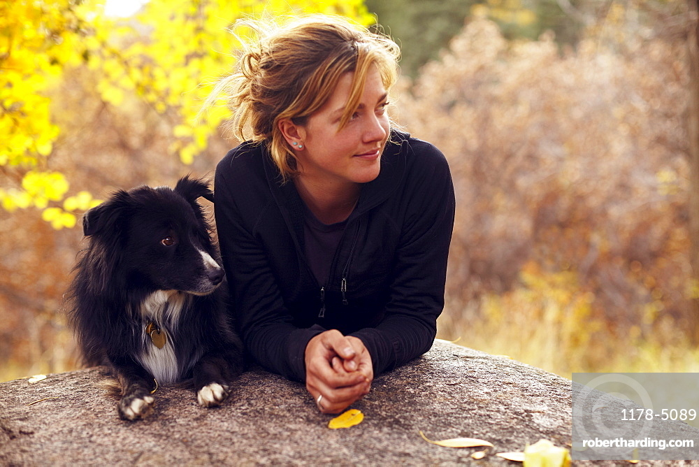 Woman and her collie leaning on rock, Colorado, USA