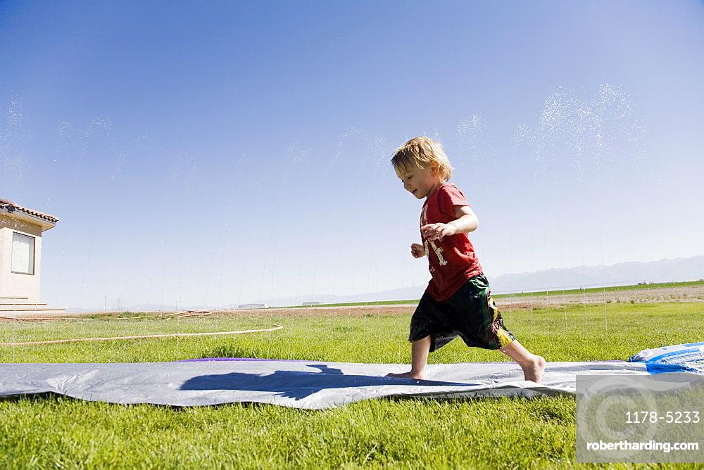 Toddler boy (2-3) running on field, Colorado, USA