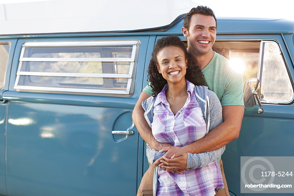 Young couple in front of mini van during road trip