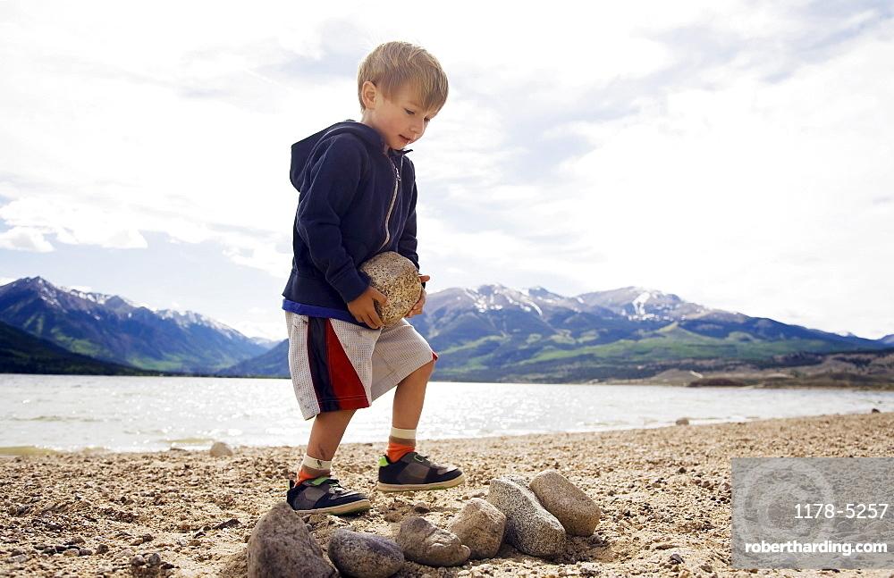 Boy (2-3) carrying rock on beach, Colorado, USA