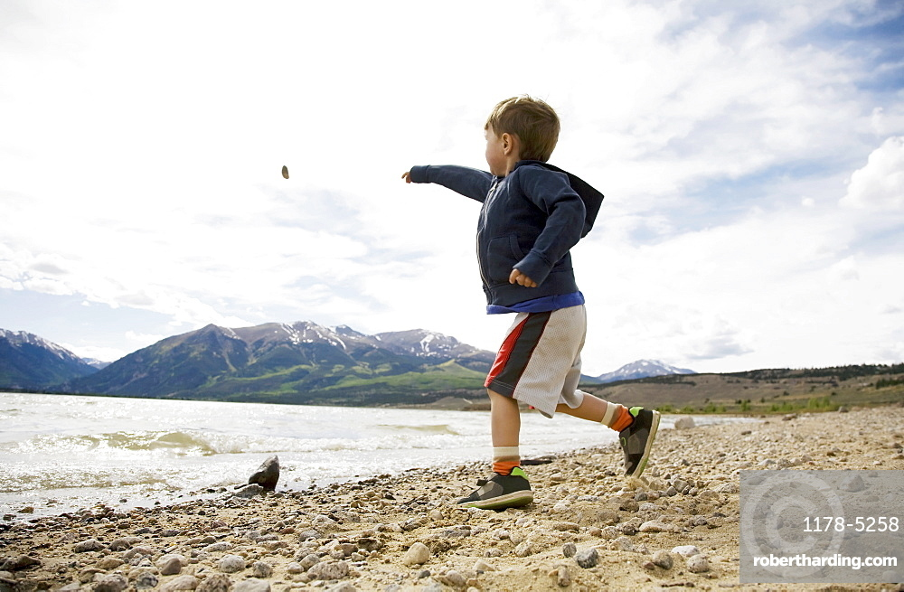 Boy (2-3) throwing rock in lake, Colorado, USA