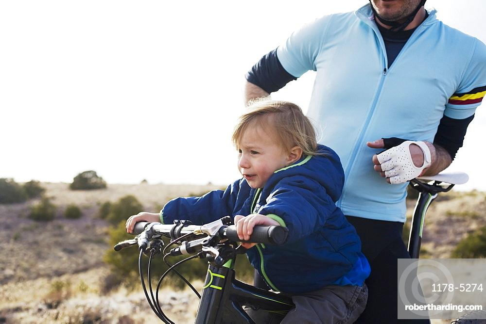 Toddler boy (2-3) with father on mountain bike, Colorado, USA