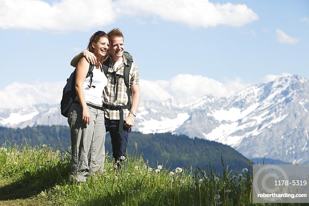 Switzerland, Leysin, Hikers standing on meadow in Alps, Switzerland, Leysin
