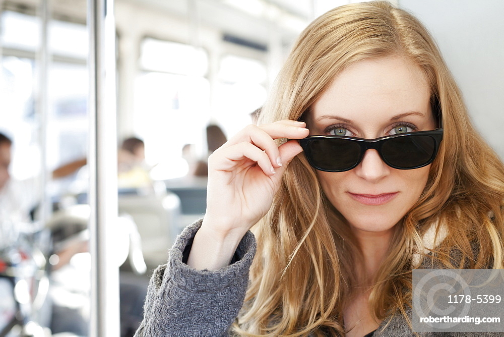 Portrait of woman wearing sunglasses in subway train