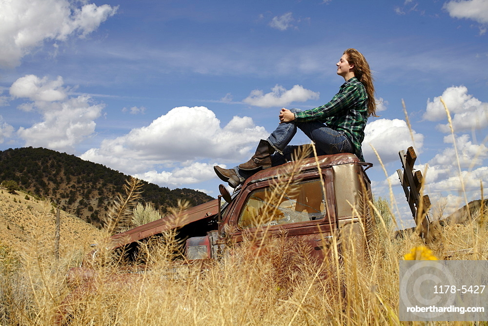 USA, Colorado, Woman resting on roof of abandoned truck in desert