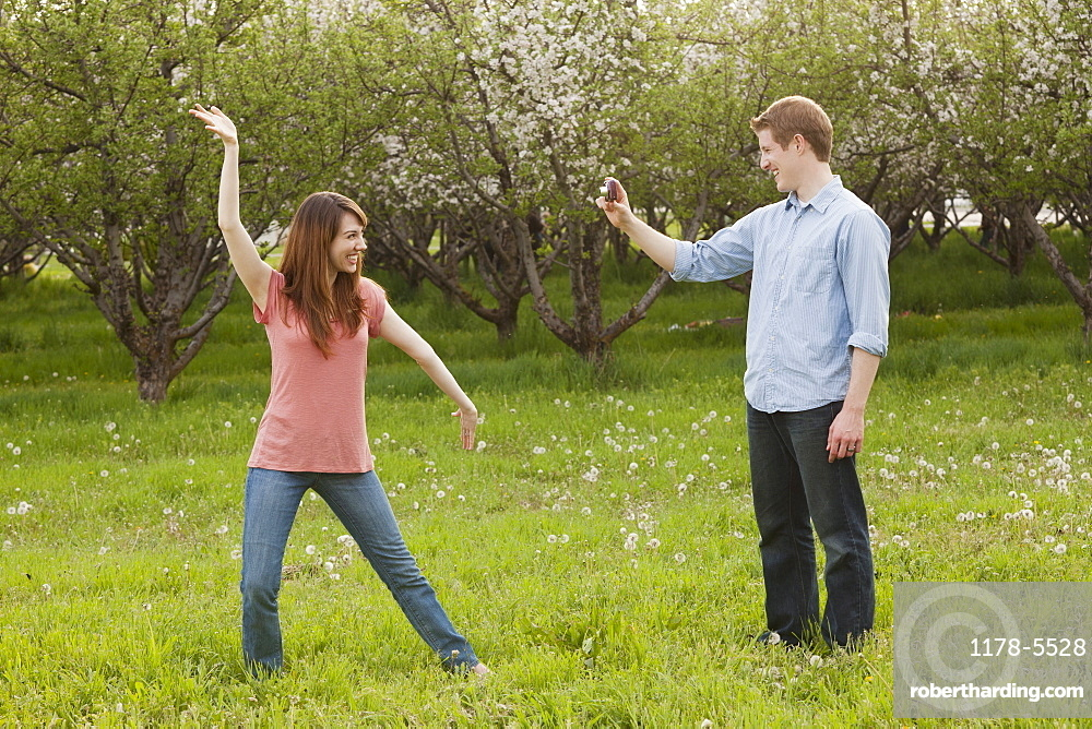 USA, Utah, Provo, Young man photographing young woman in orchard