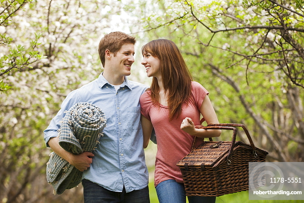 Young couple with picnic basket in orchard