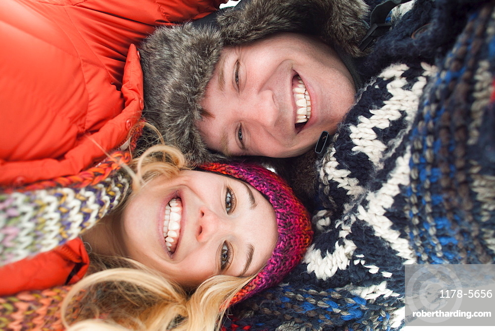 Portrait of young couple lying in snow
